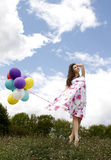 Woman with baloons. Beautiful woman with baloons in the field Stock Image