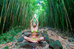 Woman Bamboo Yoga. Woman in green bikini doing yoga on bamboo path Royalty Free Stock Photography