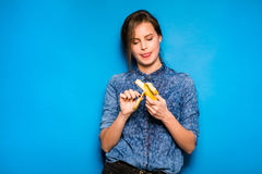 Woman with banana in hands on blue background Royalty Free Stock Images