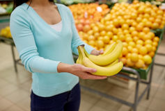 Woman with bananas at grocery store. Shopping, sale, food, consumerism and people concept - woman with bananas at grocery store Stock Photography