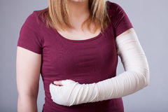 Woman with bandaged arm. A closeup of a woman with a hurt bandaged arm royalty free stock images