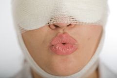 Woman with bandaged face blowing a kiss. Close-up portrait of a woman with a bandaged face blowing a kiss royalty free stock images