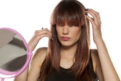 Woman with bangs. Young woman adjusting her bangs in front of a mirror royalty free stock images