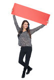 Woman with banner. Full length young woman holding red blank cardboard over head, over white background Royalty Free Stock Image