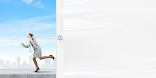 Woman with banner. Young businesswoman running and pulling white blank banner Royalty Free Stock Image