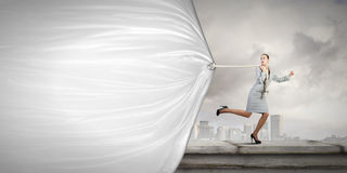 Woman with banner. Young businesswoman running and pulling white blank banner Stock Images