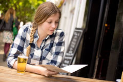 Woman at bar reading menu Royalty Free Stock Image