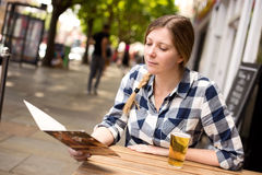 Woman at bar reading menu Stock Images