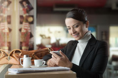 Woman at the bar texting with her mobile phone Royalty Free Stock Photo