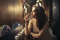 Woman at a bar. Young woman drinking alone at a bar Stock Image