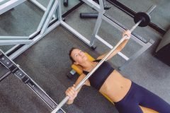 Woman with barbell on a bench press training Royalty Free Stock Images