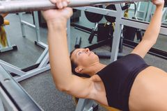 Woman with barbell on a bench press training Stock Photography