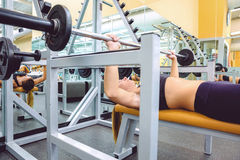Woman with barbell on a bench press training Stock Image