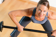 Woman with barbell in gym stock images