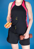 Woman with barbell and hot dog Stock Photography