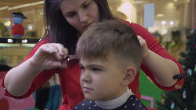 Woman barber cut hair angry upset little boy. Children barbershop. Child client sitting on the chair in beauty salon. Adult hair cutter using comb and scissors stock video