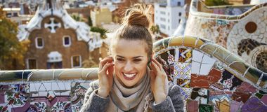 Woman in Barcelona listening audioguide while sitting on bench. Barcelona signature style. smiling trendy tourist woman in coat in Barcelona, Spain listening Stock Photography