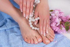 Free Woman Bare Feet And Hands With French Manicure And Pedicure In Spa Salon On Blue Blue Towel With Decorative Flower And Pearls Stock Photography - 144503862