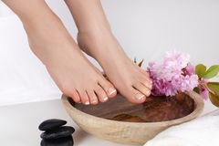 Woman bare feet with french pedicure in spa salon with wooden bowl and pink flower and stone decoration. Beautiful young gently girl bare feet with french stock photos
