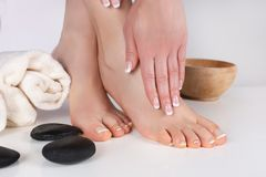 Woman bare feet and hands with french manicure and pedicure nails polish on towel in spa salon. Young beautiful gently female bare feet and hands with french royalty free stock photography