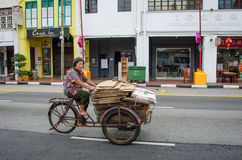 Woman in bare feet transports goods with an old, rusted tricycle Singapore Stock Images