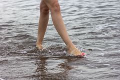 Woman bare foot walking on the summer beach. Walking along wave of sea water and sand on the beach, close-up. stock photography