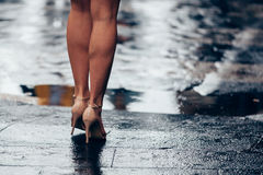 Woman in bare legs with heels in front of puddle. Woman legs walking and waiting with heels and umbrella Royalty Free Stock Image