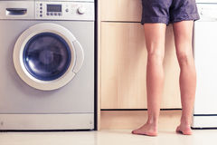 Woman with bare legs in kitchen. Woman with bare legs is standing next to her washing machine doing housework Royalty Free Stock Photo