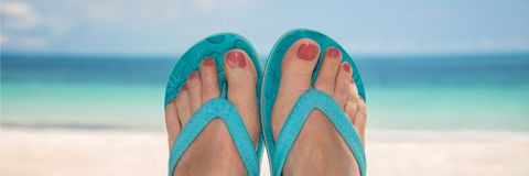 Woman bare sandy feet with blue flip flops, beach in the background royalty free stock image