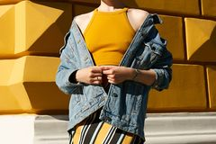A woman with bare shoulders in a denim jacket and in a yellow to royalty free stock images
