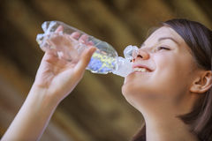 Woman with bare shoulders drinks from bottle of water Stock Photography