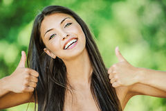 Woman with bare shoulders happily. Portrait of young beautiful woman with bare shoulders happily raises his thumb up and smiling, on green background summer Stock Photography