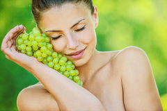 Woman with bare shoulders holding. Portrait of young beautiful woman with bare shoulders holding grapes, on green background summer nature Royalty Free Stock Image