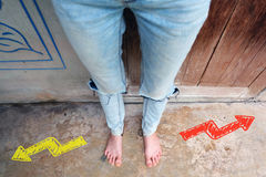 Woman Barefeet Standing with Yellow or Red Drawn Different Direction Arrows on the Concrete Background. Great For Any Use Stock Photography