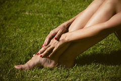 Woman barefoot legs on grass Stock Images