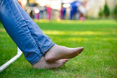 Woman Barefoot Legs on the Green Grass in Garden Stock Photos