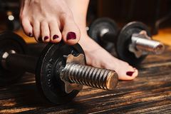 Woman barefoot standing with one feet on a dumbbell royalty free stock photos