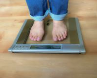 Woman barefoot standing on weight scale royalty free stock photos