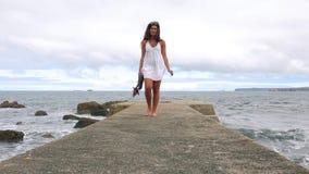 Woman barefoot walking along of empty pier stock video