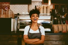 Cheerful barista in her coffee shop stock images