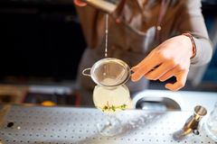 Woman bartender pouring cocktail into glass at bar. Alcohol drinks, people and luxury concept - woman bartender poring cocktail from shaker through strainer into stock image