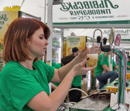 Woman bartender pours Lvivske beer outdoor in Kiev, Ukraine. Royalty Free Stock Photography