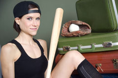 Woman with baseball bat glove ball luggage. Portrait of sexy young woman with baseball bat and hat, suitcases in background Royalty Free Stock Photos