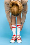 Woman in baseball boots stretching Stock Image