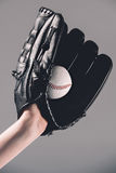 Woman in baseball glove holding ball on grey Royalty Free Stock Photography