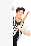Woman in baseball jersey posing behind a panel. Vertical shot of a young woman in a baseball jersey posing behind a blank billboard with a baseball bat in her Stock Photos