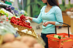 Woman with basket buying peppers at grocery store Stock Image