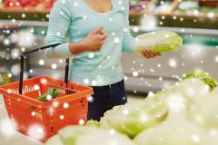 Woman with basket and chinese cabbage at grocery Stock Images
