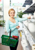 Woman with basket choosing flower pot in shop Stock Image