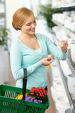 Woman with basket choosing flower pot in shop Royalty Free Stock Photos